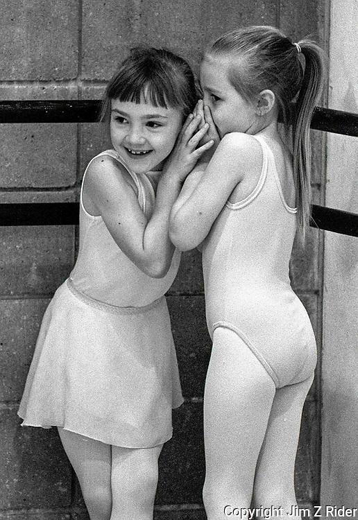 Two little dancers share a bit of gossip during a ballet class.