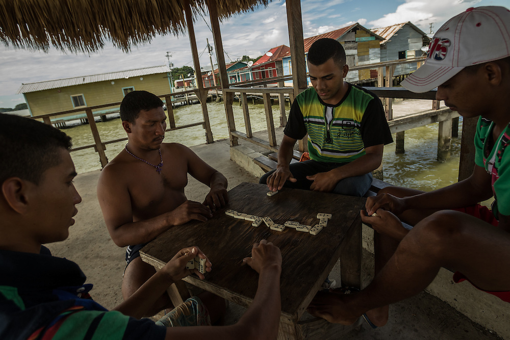 """CEUTA, VENEZUELA - AUGUST 28, 2014: Fishermen play dominoes after work in Ceuta, a community of """"palafitos"""", shacks built on posts above Lake Maracaibo, where much of Venezuela's oil reserves are concentrated. Despite being so close to wells that have brought Venezuela tremendous oil wealth, residents of Ceuta live in impoverished conditions. PHOTO: Meridith Kohut for The New York Times"""