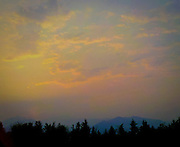 A forest fire in the Olympic mountains gives the air a metalic looking warm glow after sunset as viewed from the Kitsap Peninsula, WA, USA