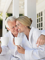 Couple sitting on verandah holding coffee cups