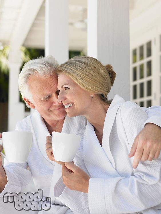 Couple sitting on verandah holding coffee cups