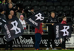 Ospreys fans wave flags before the match<br /> <br /> Photographer Simon King/Replay Images<br /> <br /> Guinness PRO14 Round 19 - Ospreys v Leinster - Saturday 24th March 2018 - Liberty Stadium - Swansea<br /> <br /> World Copyright © Replay Images . All rights reserved. info@replayimages.co.uk - http://replayimages.co.uk