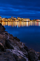 The lights of downtown buildings are reflected in the calm water of the Inner Harbour in Victoria, BC Canada