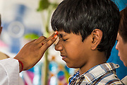 "29 SEPTEMBER 2012 - NAKORN NAYOK, THAILAND:  A boy winces as a Brahman priest anoints him during observances of Ganesh Ustav at Wat Utthayan Ganesh, a temple dedicated to Ganesh in Nakorn Nayok, about three hours from Bangkok. Many Thai Buddhists incorporate Hindu elements, including worship of Ganesh into their spiritual life. Ganesha Chaturthi also known as Vinayaka Chaturthi, is the Hindu festival celebrated on the day of the re-birth of Lord Ganesha, the son of Shiva and Parvati. The festival, also known as Ganeshotsav (""festival of Ganesha"") is observed in the Hindu calendar month of Bhaadrapada, starting on the the fourth day of the waxing moon. The festival lasts for 10 days, ending on the fourteenth day of the waxing moon. Outside India, it is celebrated widely in Nepal and by Hindus in the United States, Canada, Mauritius, Singapore, Thailand, Cambodia, Burma , Fiji and Trinidad & Tobago.     PHOTO BY JACK KURTZ"