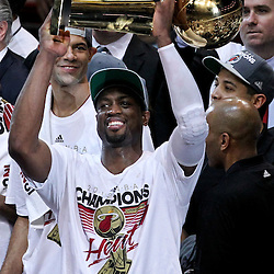 Jun 21, 2012; Miami, FL, USA; Miami Heat shooting guard Dwyane Wade (3)celebrates with the Larry O'Brien Trophy after winning the NBA championship in game five of the 2012 NBA Finals against the Oklahoma City Thunder at the American Airlines Arena. Miami won 121-106. Mandatory Credit: Derick E. Hingle-US PRESSWIRE