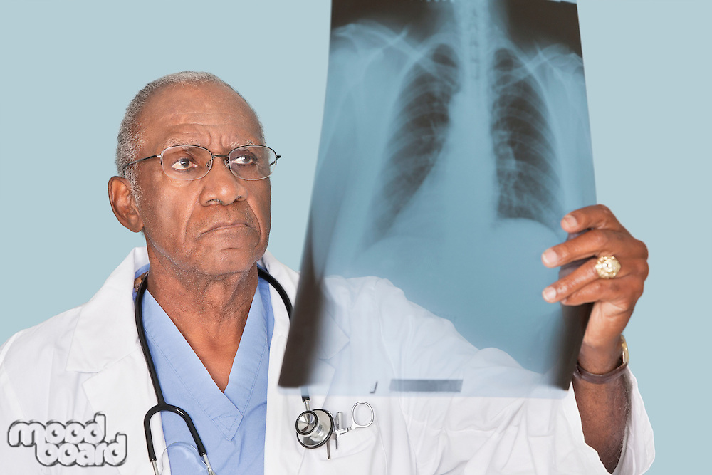 African American male doctor analyzing x-ray report over light blue background