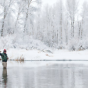 A fly fisherman plays a trout during a winter day on the South Fork of the Snake River, Idaho.