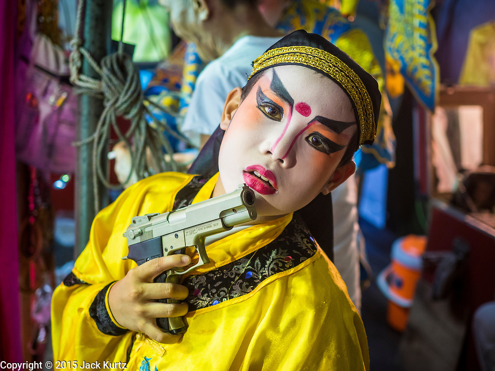 """14 MAY 2015 - BANGKOK, THAILAND: A child who performs in the Chinese opera with his toy gun backstage at the Pek Leng Keng Mangkorn Khiew Shrine in the Khlong Toey slum in Bangkok. Chinese opera was once very popular in Thailand, where it is called """"Ngiew."""" It is usually performed in the Teochew language. Millions of Chinese emigrated to Thailand (then Siam) in the 18th and 19th centuries and brought their culture with them. Recently the popularity of ngiew has faded as people turn to performances of opera on DVD or movies. There are still as many 30 Chinese opera troupes left in Bangkok and its environs. They are especially busy during Chinese New Year and Chinese holiday when they travel from Chinese temple to Chinese temple performing on stages they put up in streets near the temple, sometimes sleeping on hammocks they sling under their stage. Most of the Chinese operas from Bangkok travel to Malaysia for Ghost Month, leaving just a few to perform in Bangkok.       PHOTO BY JACK KURTZ"""