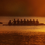 An eight crew prepare to row during a beautiful sunrise on Lake Karapiro, near Cambridge, Waikato. Many national and international rowing competitions are held on Lake Karapiro which is also the home of The Rowing New Zealand High Performance Centre. Lake Karapiro hosted the 2010 World Rowing Championships. Lake Karapiro, Waikato,  New Zealand. 14th December 2010. Photo Tim Clayton