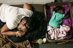 September 11, 2017 - St. Petersburg, Florida, U.S. - MICHELE SNELLING, left, sleeps on couch cushions next to her daughter LAURYN, 4 months old in a make shift bed in a suitcase at John Hopkins Middle School in the early morning hours of Monday. The school filled classrooms and hallways with  people evacuating before Hurricane Irma makes landfall. The shelter welcomes people from the area with pets and those with special needs. (Credit Image: © Eve Edelheit/Tampa Bay Times via ZUMA Wire)