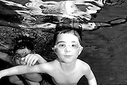 3 year old boy underwater in a swimming pool
