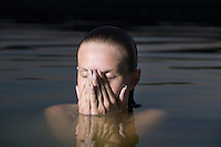 Young woman covers her face with her hands in water