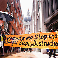 London, UK - 15 June 2012: protesters holding a banner reading ' Vedanta plc stop the killings! Stop the destruction' during the Carnival of Dirt. The dome of St. Paul's cathedral on the background. More than 30 activist groups from London and around the world have come together to highlight the alleged illicit deeds of mining and extraction companies.