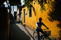 A man rides his bicycle down the old streets of Hoi An in central Vietnam.