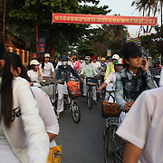 School children leave school on bikes in Hoi An, Vietnam. Hoi An is an ancient town and an exceptionally well-preserved example of a South-East Asian trading port dating from the 15th century. Hoi An is now a major tourist attraction because of its history. Hoi An, Vietnam. 5th March 2012. Photo Tim Clayton