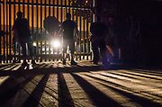 The headlights of a police car are directed on five young people behind a gate, 'Scumoween', Whitgift Street, Lambeth, London, UK, 31 October, 2015