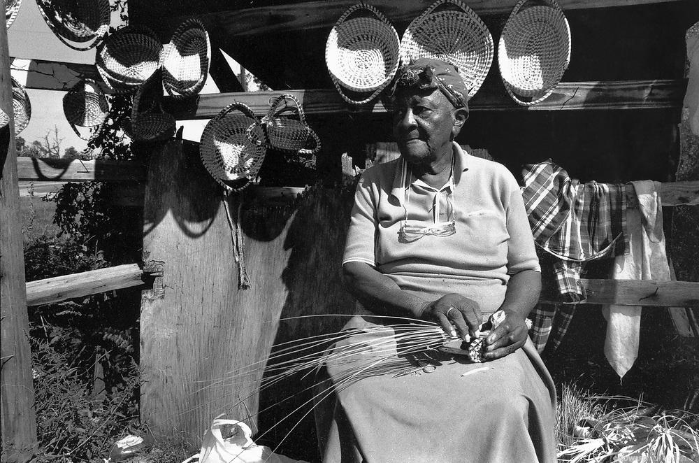 An elderly black woman weaves baskets by the roadside, South Carolina.