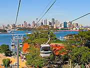 """See downtown Sydney from Taronga Zoo Sky Safari cable car, New South Wales (NSW), Australia. Sydney Opera House was opened in 1973 on Bennelong Point in Sydney Harbour. It was conceived and largely built by Danish architect Jørn Utzon after a long gestation starting with his competition-winning design in 1957. Utzon received the Pritzker Prize, architecture's highest honor, in 2003: """"There is no doubt that the Sydney Opera House is his masterpiece… one of the great iconic buildings of the 20th century, an image of great beauty that has become known throughout the world – a symbol for not only a city, but a whole country and continent."""" The Sydney Opera House was honored as a UNESCO World Heritage Site in 2007."""