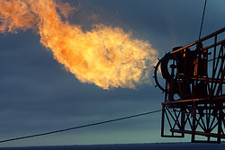 Stock photo of a gas flare burning off waste gas on an offshore drilling rig.