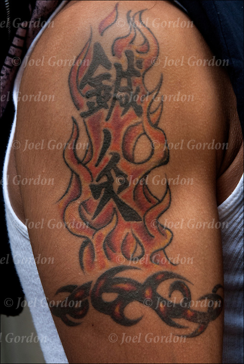 Close up of oriental tribal theme tattoos on  his shoulder and arm<br />