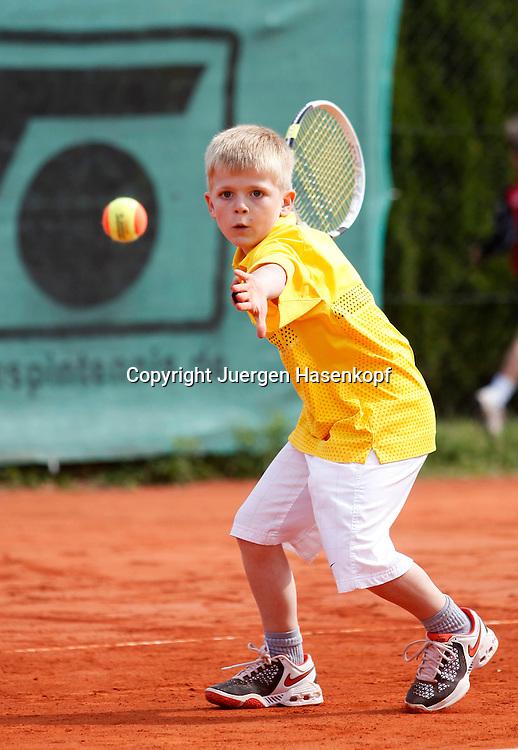 Midcourt Tennis Turnier fuer Kinder,kleiner Junge spielt Tennis,schaut konzentriert auf den Ball, Konzentration,Vorhand,.Einzelbild,Aktion,Ganzkoerper,Hochformat,