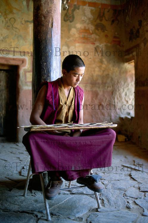 Inde. Province du jammu et Kashmir. Ladakh. Monastere bouddhiste de Tiksey. Moine à la lecture d'un livre de priere. // India. Province of  Jammu Cachemire. Ladakh . Monastère buddhist monastery of Tiksey. Monk reading a prayer book.