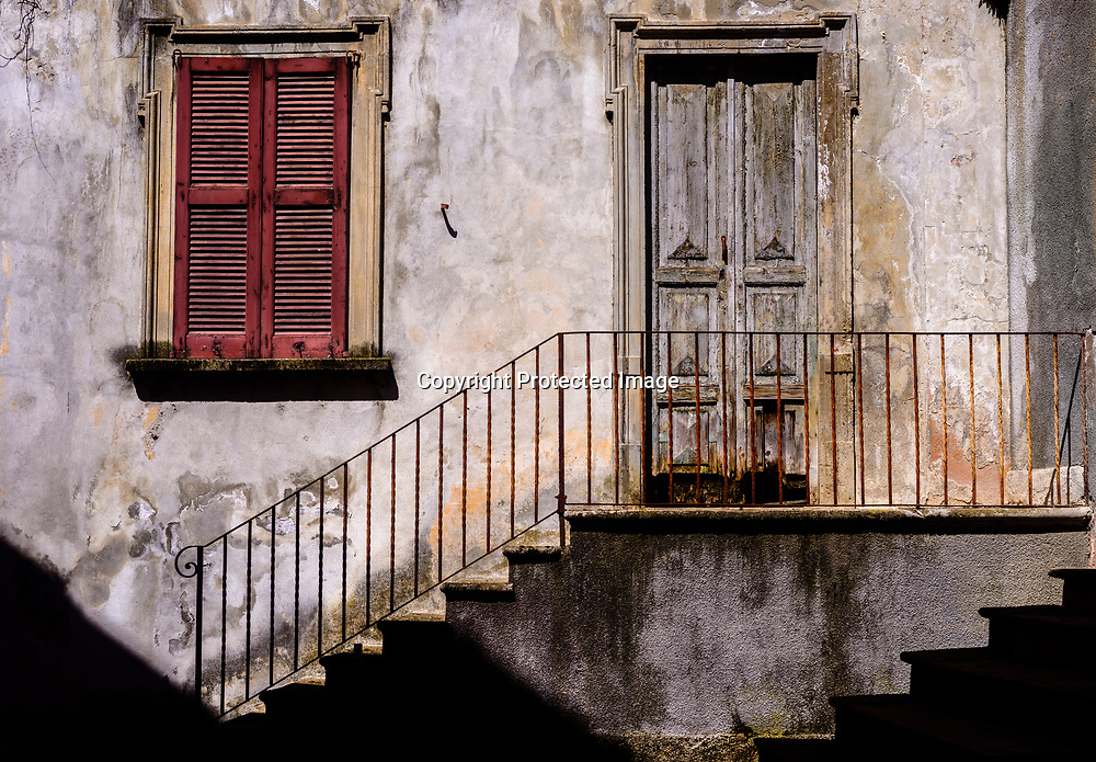 Traditional sun-lit rustic Italian architecture facade with stairs alongside iron railing leading to worn out stairs and wooden door