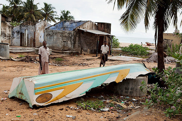 Fishermen in front of a wrecked ship that is still lying on the beach. 75% of the country's fleet was destroyed. Kalmunai, October 2009.
