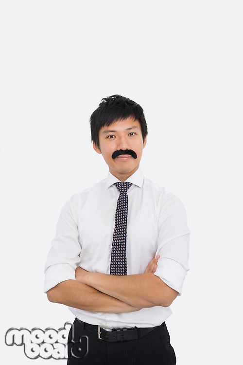 Portrait of confident businessman with fake mustache over white background