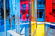 Framed by multicolored glass panels, City workers walk along Lime Street during the lunchtime break in the City of London  the capital's financial district, on 17th June 2019, in London, England. The artwork is entitled 'Series Industrial Windows I' by<br /> Marisa Ferreira and is part of Sculpture in the City 2019.
