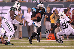 Aug 26, 2012; East Rutherford, NJ, USA; Carolina Panthers quarterback Cam Newton (1) runs with the ball while being chased by New York Jets defensive end Muhammad Wilkerson (96) and New York Jets linebacker Calvin Pace (97) during the first half at MetLife Stadium.