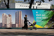 A mother walks past a regeneration project hoarding at Elephant Park, at Elephant & Castle, London borough of Southwark. Southwark Council's development partner, Lendlease is regenerating over 28 acres across three sites at the heart of Elephant & Castle, in what is the latest major regeneration opportunity in zone 1 London. The vision for the £1.5 billion regeneration is to build on the area's strengths and vibrant character in order to re-establish Elephant & Castle as one of London's most flourishing urban quarters. The Elephant & Castle regeneration is of a scale rarely seen in central London and includes almost 3,000 new homes, plus office, retail, community, leisure and restaurant space.