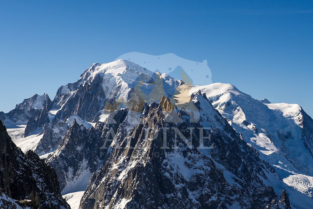 A wide-angle perspective on Mont Blanc Massif with the landmark summits of Aiguille Blanche de Peuterey, Aiguille Diable, Aiguille du Midi, Aiguille Gouter, Mont Blanc du Tacul, and Mont Maudit visible in bright sun on a cold Winter morning. Photograph taken from the glacial plateu of Aiguille Verte.