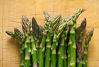 Studio still lifes of a bunch of asparagus on a cutting board.