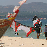 A Vietnamese instructor walks down the beach with his student carrying a surf-kite in tow.