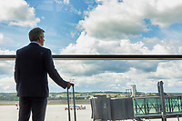 Portrait of mature businessman standing with his suitcase while looking through the window in airport