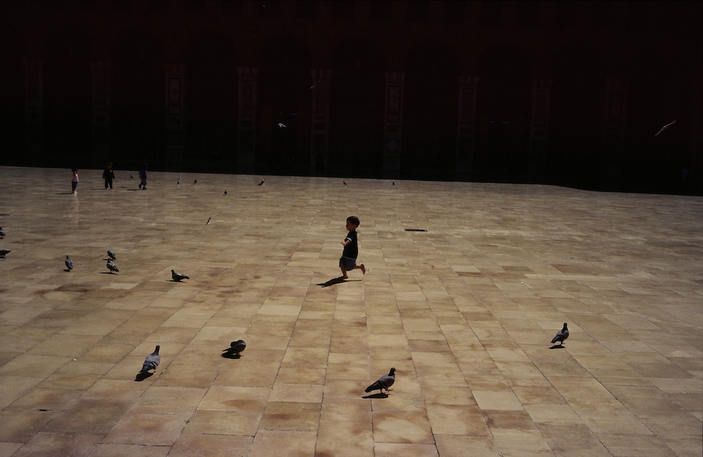 Syria, a child plays with pigeons in the yard of the Umayyad mosque in Damascus.