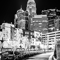 Charlotte, NC at night black and white photo with Romare Bearden Park walkway. Charlotte, North Carolina is a major city in the Eastern United States of America. Includes Bank of America Corporate Center, Bank of America Plaza, and 121 West Trade buildings.