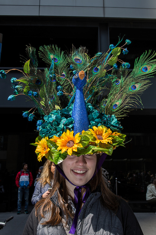 New York, NY, USA-27 March 2016. A young woman wears a hat with peacock feathers, the hat made to look like a peacock itself,  in the annual Easter Bonnet Parade and Festival.