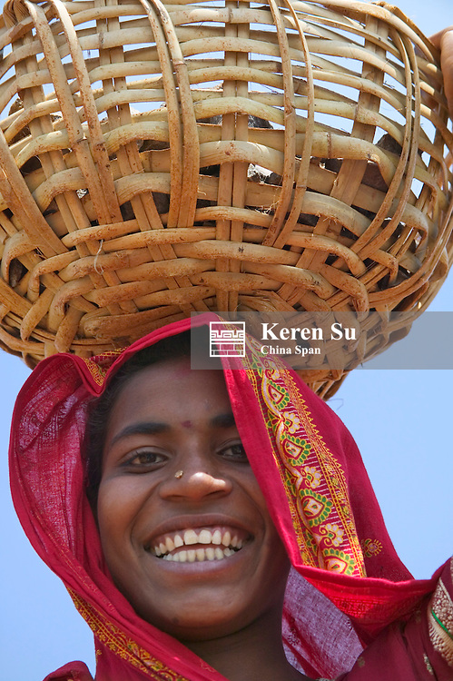 Indian woman carry basket of rocks on head to build the road in the village, Orissa, India