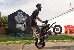 A participant in Dude Days a mini dirt-bike even rode his bike past a mural of Legendary heavyweight boxing champion Muhammad Ali, a Louisville, Ky. native, died Friday, June 3, 2016.