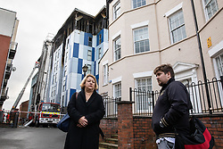 "© Licensed to London News Pictures. 16/11/2019. Bolton, UK. SANDRA RUIZ and TIAGO ALVES of Grenfell United, both of whom are former Grenfell Tower residents , at the site of the blaze . Firefighters work at the scene where a fire broke out overnight (15th/16th November 2019) at a block of flats known as "" The Cube "" , in Bolton Town Centre . At least two people are known to have been treated by paramedics at the scene of the six-story block , which is occupied by students of the University of Bolton . Photo credit: Joel Goodman/LNP"