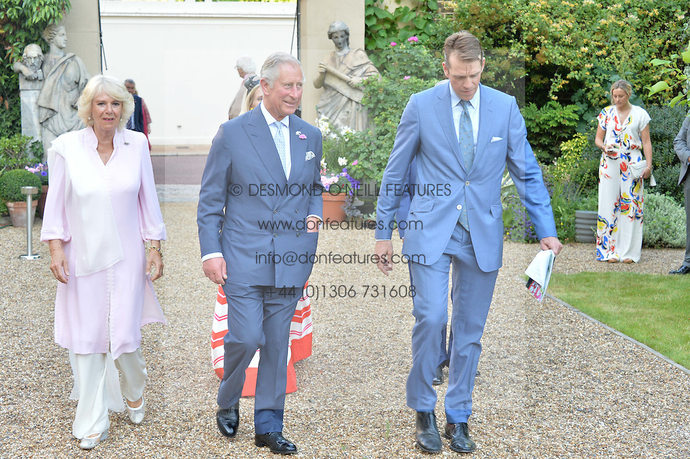 HRH THE PRINCE OF WALES, THE DUCHESS OF CORNWALL, RUTH POWYS and BEN ELLIOT at the Quintessentially Foundation and Elephant Family 's 'Travels to My Elephant' Royal Rickshaw Auction presented by Selfridges and hosted by HRH The Prince of Wales and The Duchess of Cornwall held at Lancaster House, Cleveland Row, St.James's, London on 30th June 2015.