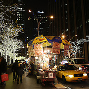 A fast food seller amongst christmas decorations on 6th Avenue, Manhattan, New York USA. 25th November 2012. Photo Tim Clayton