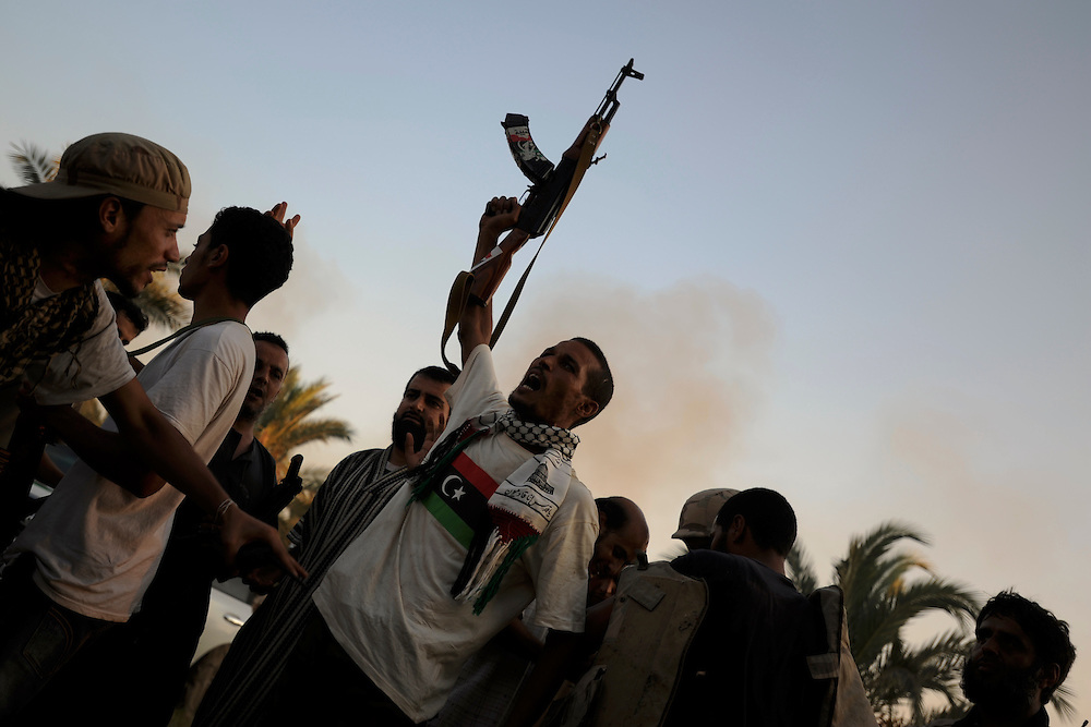 A group of rebel fighters celebrate the successful take of Muammar Gaddafi's Bab Al Azizia compound in Tripoli.