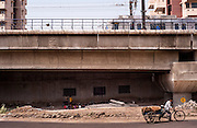 22nd April 2013, Shakarpur, New Delhi, India.  Children study while a metro train passes overhead at a makeshift school under a metro bridge near the Yamuna Bank Metro station in Shakarpur, New Delhi, India on the 22nd April 2013. <br /> <br /> Rajesh Kumar Sharma (40) and Laxmi Chandra (45), started this makeshift school a year ago. Five days a week, he takes out two hours to teach when his younger brother replaces him at his general store in Shakarpur. His students are children of labourers, rickshaw-pullers and farm workers. This is the 3rd site he has used to teach under privileged children in the city, he began in 1997 fifteen years ago. <br /> <br /> PHOTOGRAPH BY AND COPYRIGHT OF SIMON DE TREY-WHITE<br /> <br /> + 91 98103 99809<br /> + 91 11 435 06980<br /> +44 07966 405896<br /> +44 1963 220 745<br /> email: simon@simondetreywhite.com<br /> photographer in delhi<br /> journalist