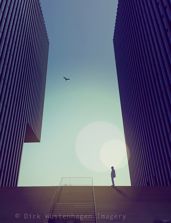 surreal urban scene - person standing between two modern buildings<br />