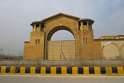 "EXCLUSIVE: FIRST PICTURES OF 'BUCKINGHAM PALACE' BUILT BY TAX FRAUDSTER IN PAKISTAN These are the first pictures of a Pakistani 'Buckingham Palace' which now lies empty after allegedly being built by a UK fraudster. Previous aerial images of Mohammed Suleman Khan's palatial property did not show the true extent of the jailed tax dodger's dreams. Khan was caged in April 2014 for four years over a tax fraud of £450,000. He was sentenced to a further ten years in 2016 for refusing to pay back £2.2million. But it's nearly 4,000 miles away in the Pakistani town of Ghorgushti, 50 miles from the capital Islamabad, Khan's ambitions still resonate with the community, many of whom have close links to the UK. There on a two-acre site a huge construction lies mostly deserted complete with high walls and imposing turrets. According to locals in the town – known as 'mini London' because of its strong links to the UK – Khan allegedly bought the site for his palace around eight years ago. However, since his jailing the site has remained unfinished and become a 'no-go area' with around a dozen armed security guards around it. When police first investigated Khan they uncovered blueprints for a 'Buckingham Palace' like building in Pakistan. Plans reportedly showed a cinema, library and servants' quarters, and private security accommodation. It was estimated the construction would have cost £2.3million, although there has been no official record of ownership. Now the luxurious surroundings of the palace appear remain but without a resident 'Don' as locals said Khan was known to inhabit them. One neighbor said: ""If you try to get into or jump from the wall they will shoot you, they often do aerial firing at night too."" The compound is closed with wooden panels barring the front gate, it has minaret security towers on each corner, which is not unusual in such big compounds elsewhere in Pakistan. Neighbors estimated there are around 30 to 40 ro"
