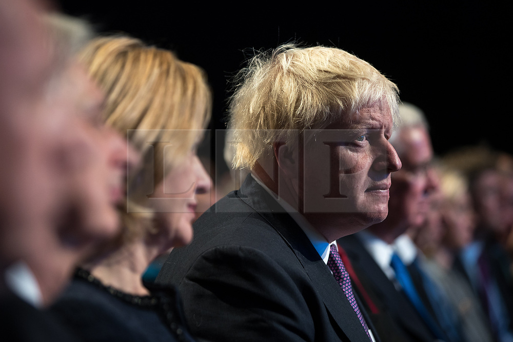 © Licensed to London News Pictures . 04/10/2017. Manchester, UK. Foreign Secretary BORIS JOHNSON listens as Prime Minister Theresa May delivers her keynote speech on the fourth and final day of the Conservative Party Conference at the Manchester Central Convention Centre . Photo credit: Joel Goodman/LNP
