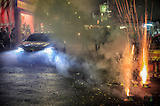A car drives down a local street as fireworks explode during a Taiwanese religious festival.